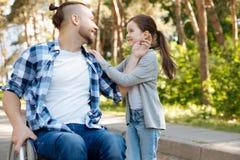 Oreille émouvante d'homme avec plaisir de sa fille Photo stock