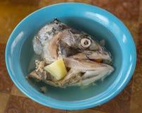 Oreille dans un plat avec la tête des poissons rouges Image stock