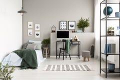 Oreiller argenté, vert et modelé sur la literie bleue sur le lit simple avec la couverture verte dans la chambre à coucher inspir images libres de droits