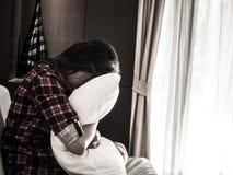 Oreiller blanc et cri d'étreinte triste de femme photos stock