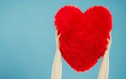 Oreiller de forme de coeur dans des mains Amour du jour de Valentine Photos libres de droits