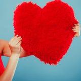 Oreiller de forme de coeur dans des mains Amour du jour de Valentine Photographie stock