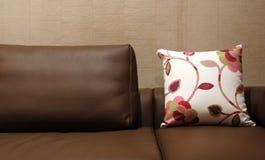 Oreiller floral sur un divan en cuir brun - intérieurs à la maison Photographie stock