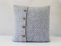 Oreiller gris tricoté avec les boutons en bois photos stock