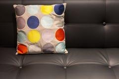Oreiller pointillé coloré sur un sofa en cuir noir image libre de droits