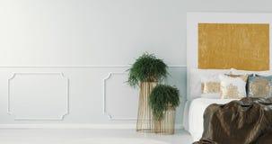 Oreillers blancs et gris avec le modèle d'or sur le lit dans l'intérieur élégant de chambre à coucher avec la peinture d'or banque de vidéos