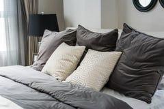 Oreillers blancs et gris sur le lit Photographie stock libre de droits