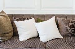 Oreillers blancs sur le sofa brun Photos libres de droits