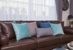 Oreillers bleus et gris sur le sofa en cuir dans le salon moderne photos stock