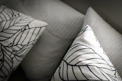Oreillers décoratifs sur le lit avec le dos de cuir photos stock