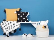Oreillers et couverture décoratifs avec des pom-poms sur un banc en bois, des pantoufles molles confortables et un panier en osie images libres de droits
