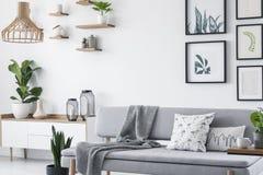 Oreillers et couverture sur le divan gris dans l'intérieur scandinave blanc de grenier avec les usines et la galerie Photo réelle photos stock