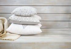Oreillers et plaid confortables sur le fond en bois clair Image stock