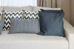 Oreillers noirs et blancs sur le sofa beige de couleur Photos stock