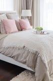 Oreillers roses sur le lit avec le plateau blanc de la fleur à la maison Image stock