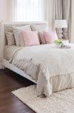 Oreillers roses sur le lit avec le plateau blanc de la fleur à la maison Photographie stock libre de droits
