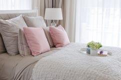 Oreillers roses sur le lit avec le plateau blanc de la fleur Photos stock