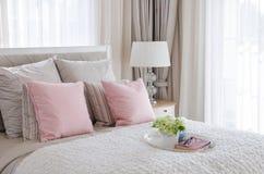 Oreillers roses sur le lit avec le plateau de la fleur Photographie stock