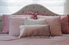 Oreillers roses sur le lit classique dans la chambre à coucher de la fille Images stock
