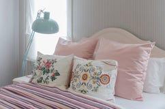 Oreillers roses sur le lit dans la chambre à coucher Images stock