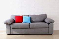 Oreillers sur le sofa gris Photographie stock libre de droits