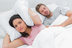 Oreilles bouleversées de bâche de femme avec l'oreiller à côté du mari ronflant Photographie stock libre de droits