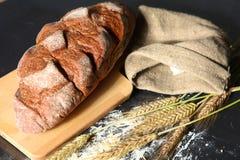 Oreilles croustillantes rustiques de pain et de blé sur une obscurité Images stock