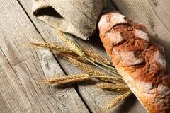 Oreilles croustillantes rustiques de pain et de blé sur une obscurité Photo stock