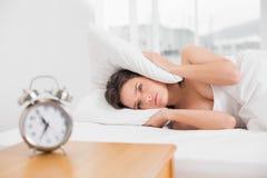 oreilles de bâche de femme avec l'oreiller dans le lit et le réveil sur la table Photos libres de droits