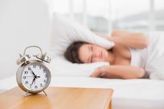 Oreilles de bâche de femme avec l'oreiller dans le lit et le réveil sur la table Photo stock