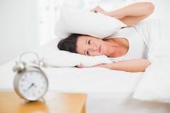 Oreilles de bâche de femme avec l'oreiller et le réveil sur la table latérale Photographie stock