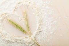 Oreilles de blé en farine sur un panneau de pain, cuites avec amour, coeur Photos libres de droits