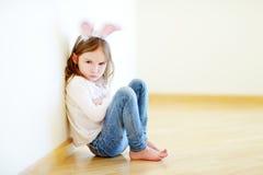 Oreilles de port très fâchées de lapin de petite fille se reposant sur un plancher images libres de droits
