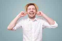 Oreilles et sourires d'homme joyeux de même que ne veut pas entendre le spoiler photographie stock
