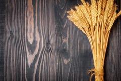 Oreilles mûres lumineuses de blé sur un fond en bois images stock