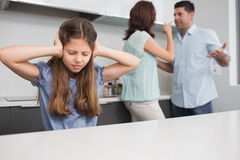 Oreilles tristes de bâche de fille tandis que parents se disputant dans la cuisine Image libre de droits