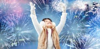 Orejeras que llevan de la niña feliz sobre el fuego artificial Fotografía de archivo libre de regalías