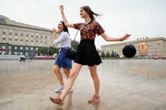 Orel, Russia, August 05, 2017: City Day. Two girls dance in pour. Ing rain in empty square with black baloon Stock Photography