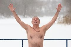 Orel, Russia - January 19, 2016: Russian epiphany feast. Naked m. An with wooden cross on his neck pray hands up horizontal Stock Photography