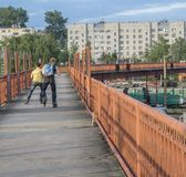 OREL (RUSSIA) in JUNE 19, 2015 - Two young boys riding on roller skates on a long wrap bridge over railroad tracks Stock Images