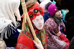 Orel, Russia, March 10, 2019: Maslenitsa selebration. Girl in red Slavonic carnival costume in crowd. Closeup stock photo