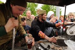Orel, Russia - May 9, 2017: Victory Day selebration. People in w. Ar uniform giving out tea and buckwheat porridge from field kitchen closeup Royalty Free Stock Photos