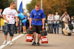 Orel, Russia, September 5, 2015: Man powerlifter carries two hea. Vy dumbbells in competition horizontal Royalty Free Stock Photos