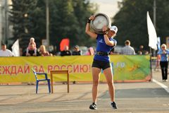 Orel, Russia, September 5, 2015: Slenred girl in shorts carrying. Heavy metal keg in competition horizontal Stock Photo