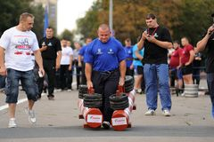 Orel, Russia, September 5, 2015: Strong male powerlifter carries. Two heavy dumbbells in competition horizontal Stock Photos