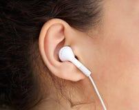 Orelha da jovem mulher com fone de ouvido Fotos de Stock Royalty Free