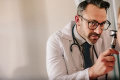 A orelha do paciente de exame do doutor masculino imagem de stock royalty free