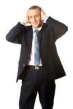 Orelhas cansados da coberta do homem de negócios com mãos Imagem de Stock
