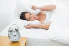 Orelhas da coberta da mulher com descanso e despertador na tabela lateral Imagem de Stock Royalty Free