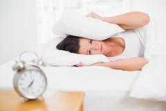 Orelhas da coberta da mulher com descanso e despertador na tabela lateral Foto de Stock